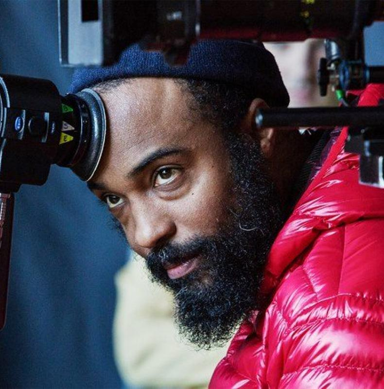 Bradford Young behind a film camera with his forehead on the camera viewfinder. He's wearing a red coat and blue knit cap.