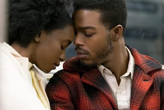 Still image from if Beale Street could Talk. Man and women sitting outside with their foreheads touching.